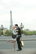 Caucasian couple kissing on bridge with Eiffel Tower in background