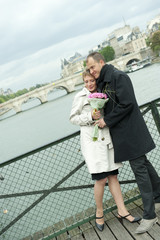 Caucasian couple hugging on bridge