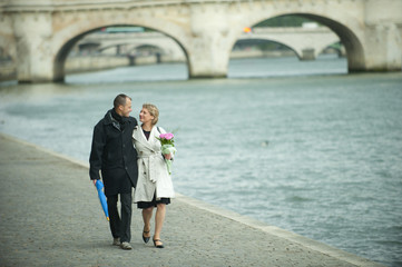 Caucasian couple walking near city river