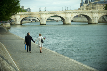 Caucasian couple holding hands and walking near river