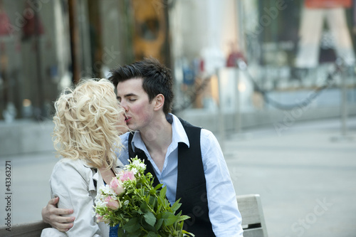 Caucasian couple kissing on bench