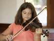 Caucasian girl practicing on violin