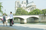 Caucasian couple walking along city river near Notre Dame
