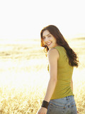 Beautiful woman standing in nature looking over her shoulder at the camera laughing