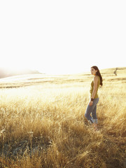Beautiful woman standing in grassy field looking out into nature