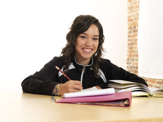 Grinning Hispanic teenager doing homework