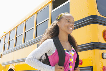 Mixed race girl standing near school bus