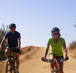 Couple riding mountain bikes on dirt road