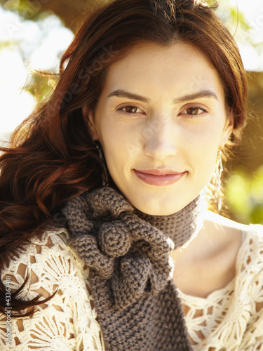 Close up of gorgeous woman in nature wearing a gray knit scarf smiling at the camera
