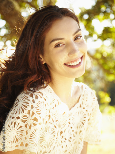 Happy beautiful woman laughing and smiling among the trees in nature