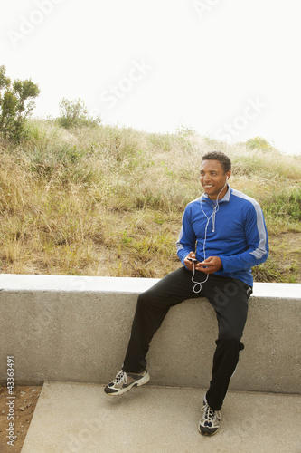 Mixed race man with mp3 player sitting on cement railing