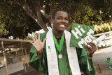 Smiling mixed race high school graduate waving with cap that says 'hi mom'