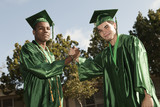 Happy high school graduates shaking hands