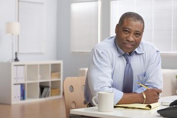 Smiling Black businessman sitting at desk in office