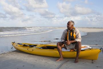 Black man sitting on beach with kayak