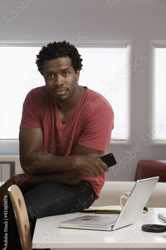 Serious Black man sitting on desk in home office