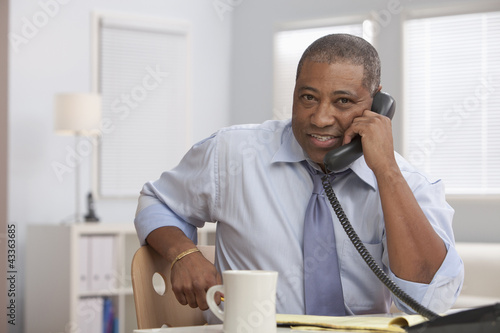 Smiling Black businessman talking on telephone at desk