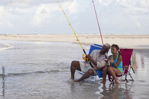 Black grandfather fishing with granddaughter on beach
