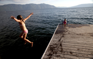 Caucasian girl jumping from pier into lake