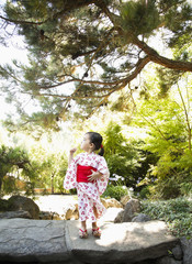 Mixed race girl in garden wearing Japanese kimono