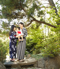 Mixed race family in garden wearing Japanese kimonos