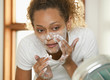 Mixed race woman washing her face