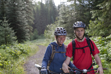 Caucasian couple standing with mountain bikes on wooded path