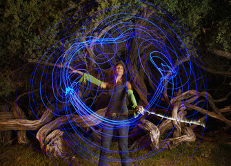 Black woman making blue light streaks in air
