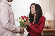 Husband giving surprised wife bouquet of roses