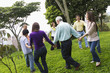 Hispanic family holding hands in a circle outdoors