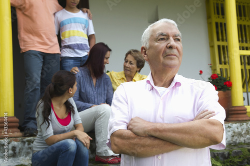 Stern Hispanic man with family in background