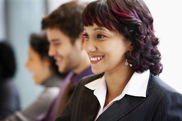 Smiling Hispanic businesswoman in office with co-workers