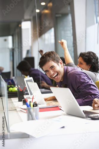 Hispanic businessman laughing in office