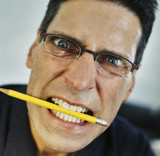 Angry businessman with pencil in mouth
