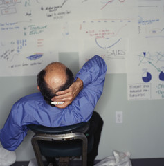 Businessman looking at drawings on office wall