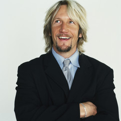 Smiling Caucasian businessman with arms crossed