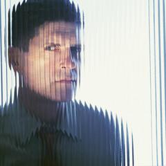 Suspicious businessman looking through glass wall