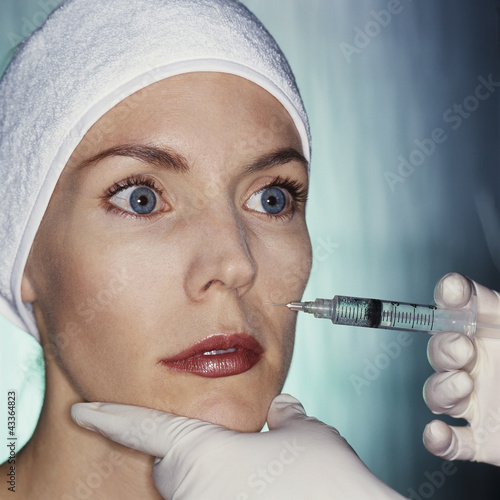 Mixed race woman having facial injection