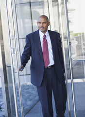 African American businessman opening glass door