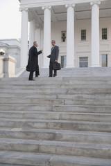 Businessman standing on steps talking