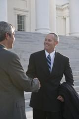 Businessmen shaking hands on steps