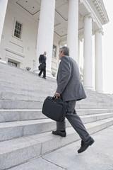 Businessman walking up steps