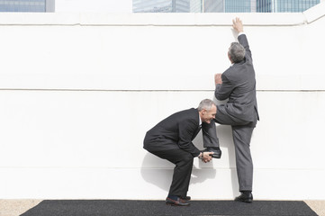 Businessman helping co-worker climb wall