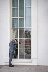 Caucasian businessman peering into window