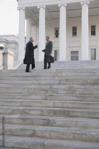Businessman standing on steps talking