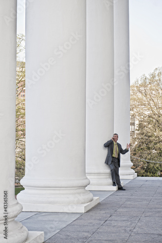 Caucasian businessman leaning against pillar talking on cell phone
