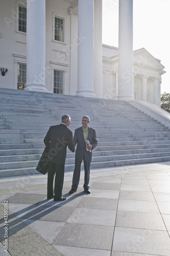 Businessmen shaking hands on steps