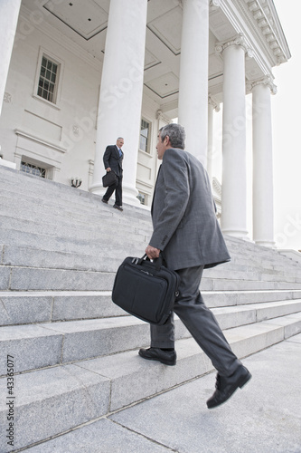 Businessman walking up steps