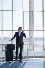 Caucasian businessman talking on cell phone in airport