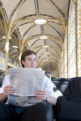 Caucasian businessman reading newspaper in airport